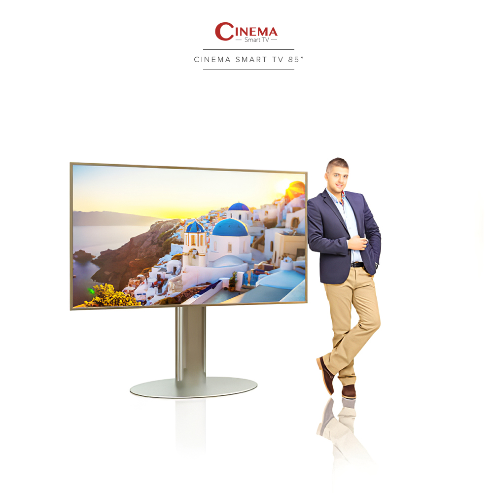 A guy leaning on a big smart TV with stainless steel casing and its oval-based floor mount.